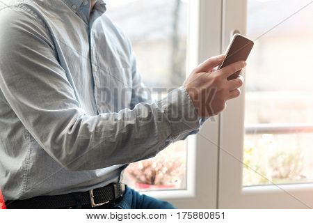 Man using his mobile phone at home next to the window