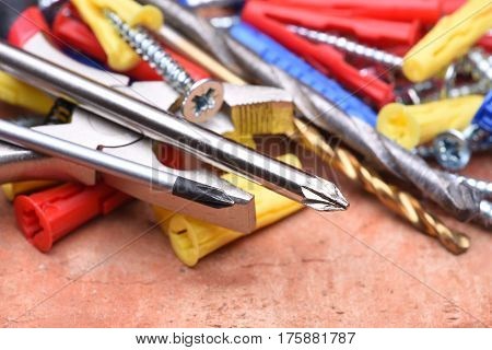 Screws plasctic dowels and tool on brick background close-up