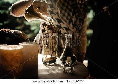 Bride And Groom Holding And Pouring  Glass Jars With Sand For Wedding Tradition Ritual At Evening Re