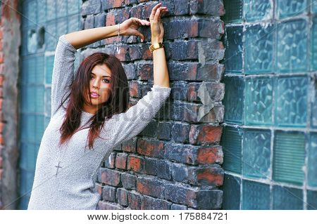 Portrait of beautiful model with tinted hair a ragged outer wind posing on brick wall background closeup