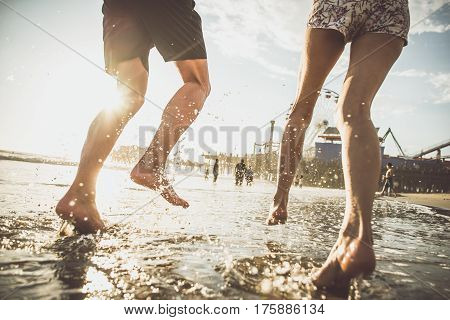 Happy couple running on the shore in the water