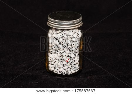 an old glass jar full of alphabet beads