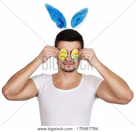 Young cheerful man with a rabbit ears holds two cookies in the form of an egg