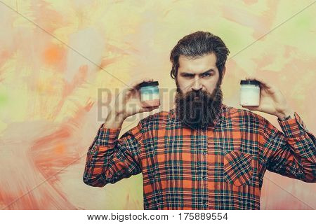 Serious Bearded Man Holding Two Cosmetic Jars