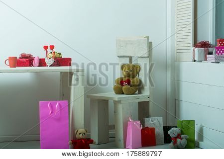 Colorful present boxes shopping bags textile and wicker hearts cute teddy bears soft toys for valentines day celebration on wooden rustic table chair window sill floor on white wall background