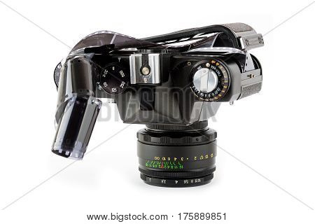 Close-up view of a opened classic manual SLR film camera with film on white background
