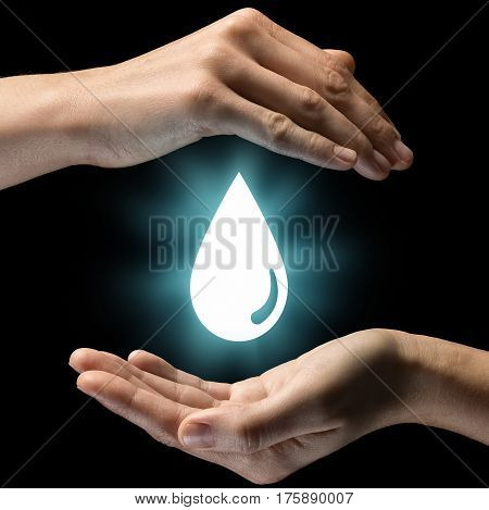 Isolated image of two hands on black background. Water drop icon in the center as a symbol of care of water resources. Concept of care of water resources.