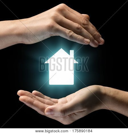 Isolated image of two hands on black background. House icon in the center as a symbol of sale rent insurance and protection of real estate. Concept of sale rent insurance and protection of real estate.