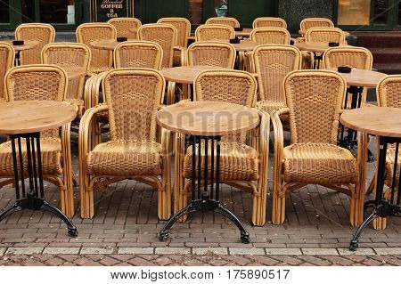 Empty dining tables and rattan wicker chairs in a street cafe Amsterdam