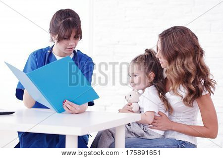 Young pediatrician doctor talking with girl and her mother