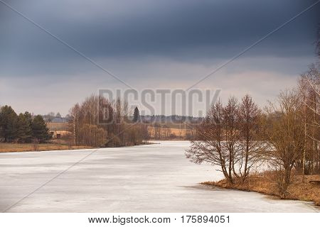 Spring Rural Scene. Lake Under Ice And Snow Melting. Cloudy Spring Day