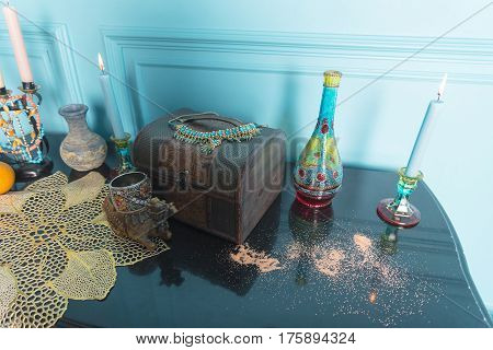 A chest candles and a bottle stand on the stele.