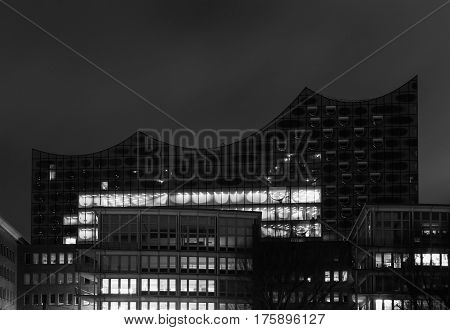 HAMBURG GERMANY - MARCH 9 2017: The elbe philharmonic hall in the harbor area Hafencity behind several office buildings at night in black and white.