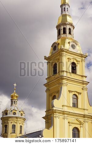 Yellow tower with a bell tower and clock on a background of gloomy sky, Sightseeing of St. Petersburg - Peter and Paul Fortress.
