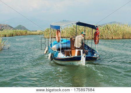 MUGLA, TURKEY - AUGUST 13, 2009: Unidentified man rides tourist boat at the Dalyan river in Mugla, Turkey.