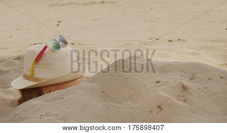 A girl buried in the sand on the beach in summer, a hat with glasses on her face.
