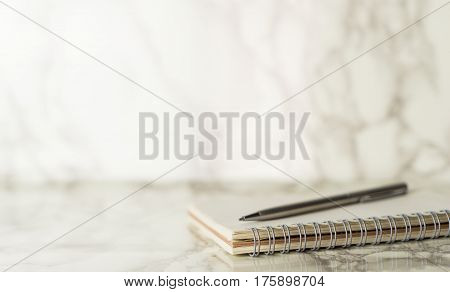 Silver pen and notebook on a marble table with copy space