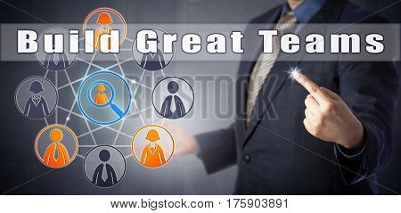 Male HR manager in blue business suit is urging to Build Great Teams. Business consulting concept and human resources management metaphor for organizing white collar staff into winning teams.