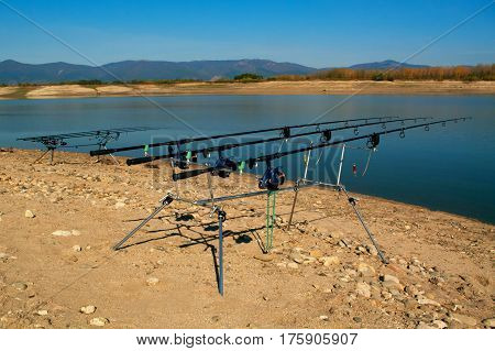 Carp fishing. Two angling scene. Looking along three carp rods towards a pond.