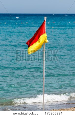 Red and yellow flag on the beach on the background of the sea