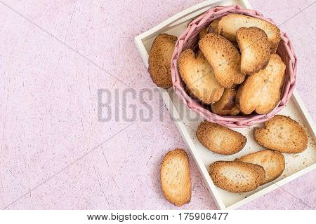 Wicker basket with homemade rusks on a white tray on a pink background.