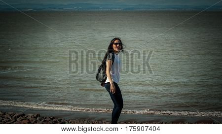 Young woman enjoying freedom feeling happy at beach in Minehead Somerset Uk.