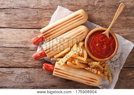 Grilled Hot Dog Rolls With French Fries And Tomato Sauce Close-up. Horizontal Top View