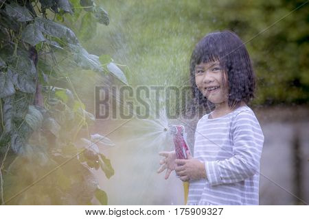 asian children playing water splashing frome a hose with happiness face in home garden