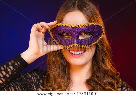 Holidays people and celebration concept. Closeup woman face with carnival violet mask on dark background.