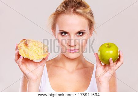 Woman holds in hand cake sweet bun and apple fruit choosing trying to resist temptation make the right dietary choice. Weight loss diet dilemma gluttony concept.