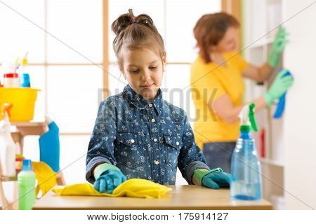 child little girl and her mother cleaning living room at home