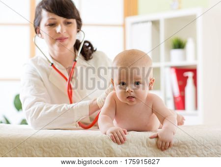 Female doctor pediatrician checking baby infant patient