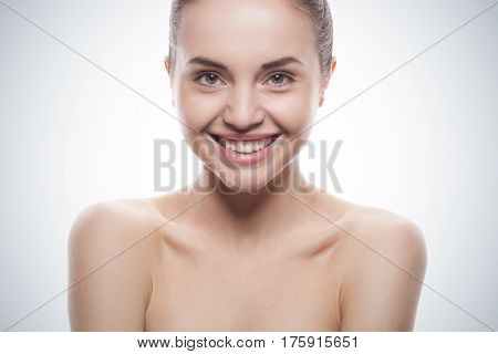 closeup portrait of young smiling woman with clean fresh skin isolated on bue gradient studio background