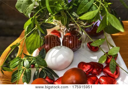 Plastic salver with Easter eggs and chocolate hearts,bouquet of periwinkle with ladybug on leaf