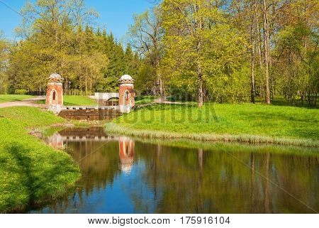 Spring landscape with river and old bridge in the park