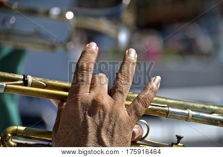 Closeup of the extended  fingers of a male trumpet player in concert.