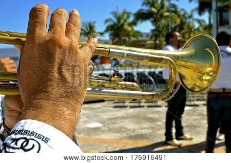 Closeup of the fingers of a male trumpet player in a Mexican city