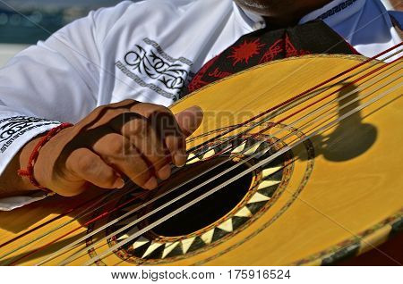 The fingers of a musician strum the strings of a guitar.