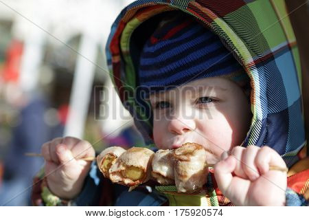 Boy biting grilled potato on the street
