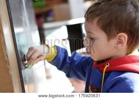 Kid draws a chalk on a blackboard