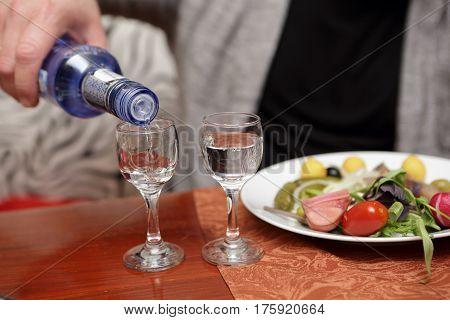 Person pouring vodka into glasses in a pub