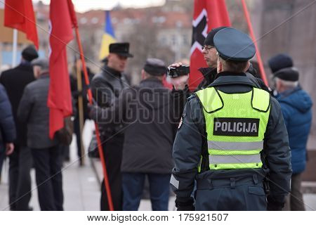 VILNIUS LITHUANIA - MAR 11: Police officers on duty in a nationalist rally at Gedimino Avenue on Re-Establishment of Independence Day on March 11 2017 in Vilnius Lithuania