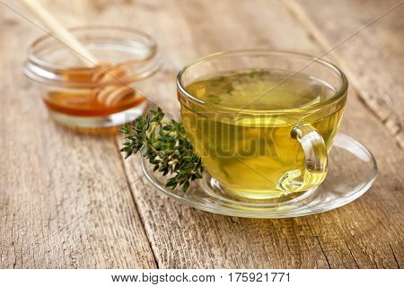 thyme tea in glass cup sprig of fresh thyme honey on the old wooden background