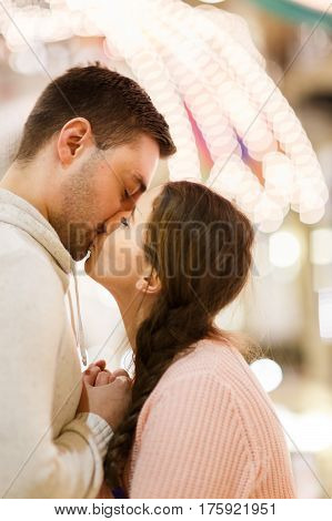 Romantic photo of kissing couple enamored at mall