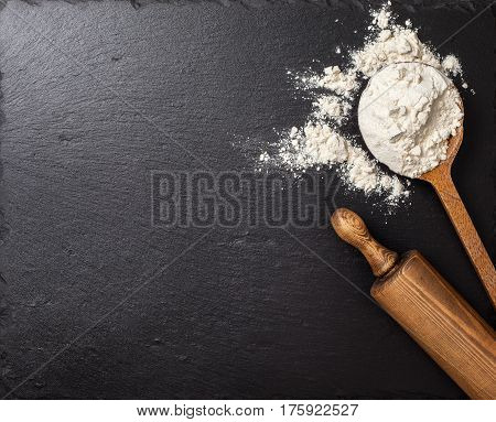 А wooden spoon with flour a rolling pin on a black slate background. Top view selective focus