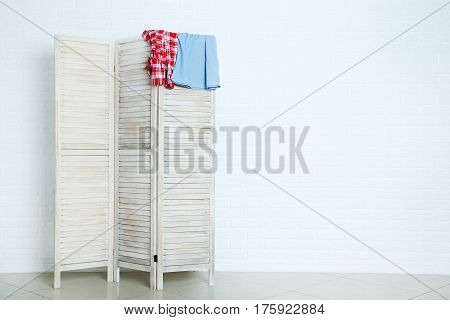 Clothes Hanging On Folding Screen On Brick Wall Background