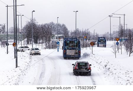 UMEA, SWEDEN ON MARCH 02. View of a modern street, road and the traffic in snowy condition on March 02, 2017 in Umea, Sweden. Signs, lampposts and buildings. Editorial use.