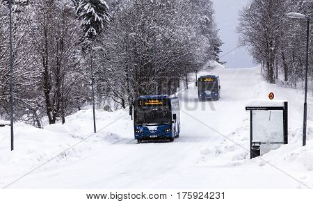 UMEA, SWEDEN ON MARCH 02. View of buses, a bus stop along a snowy road on March 02, 2017 in Umea, Sweden. Hill and trees in the background. Editorial use.