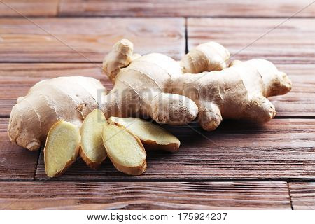 Ginger root on brown wooden table, close up