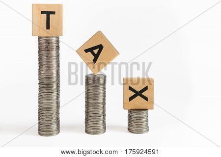 Rows of coin stacks with toy blocks symbolizing taxation.